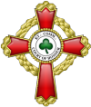 A passion cross with fancy arms with a trefoil embroidered in green in the center
