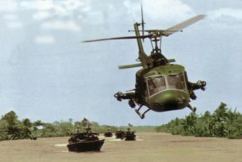 Photograph of a combat helicopter flying over a river